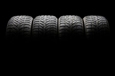 Studio shot of a set of four black car tires lined up horizontally in a dark ambient on black background Stock Photo-min