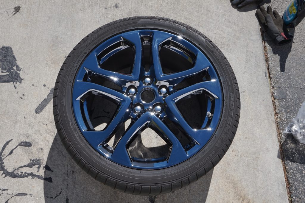 black chrome wheel with tire facing sky