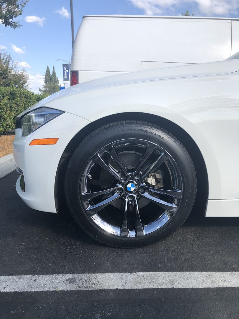 white bmw with black chrome rims parked